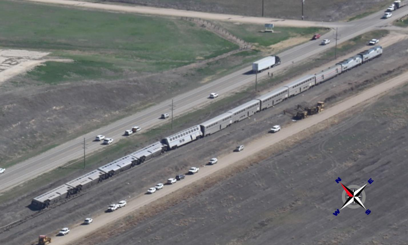 Aerial photograph of derailed Amtrak train shows the last four cars on their sides on the north side of the main track.