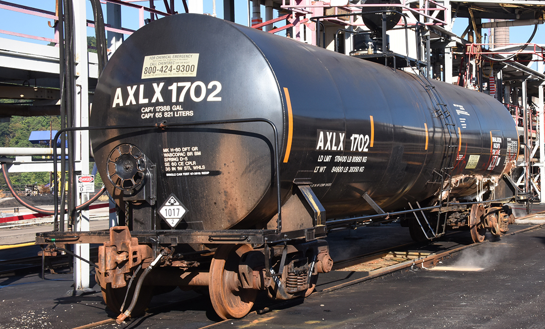 Tank car AXLX 1702 parked near a loading rack.