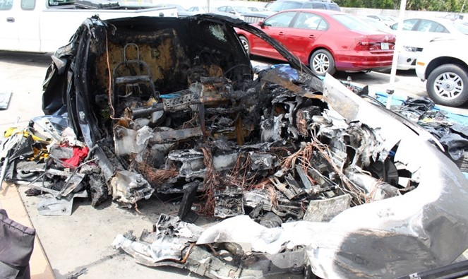 Photo of the remains of Tesla Model S at storage yard.