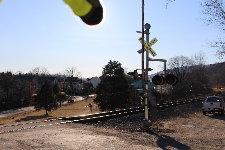 Southbound view of highway–rail grade crossing showing active warning devices