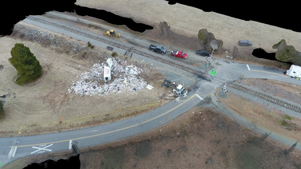 Aerial view of the highway-railroad grade crossing, truck chassis, body, and debris at final rest.