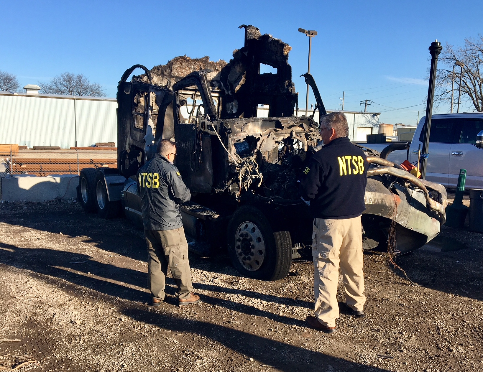 NTSB investigators examining the damaged and burnt 2016 Kenworth  truck-tractor (the Pioneer truck