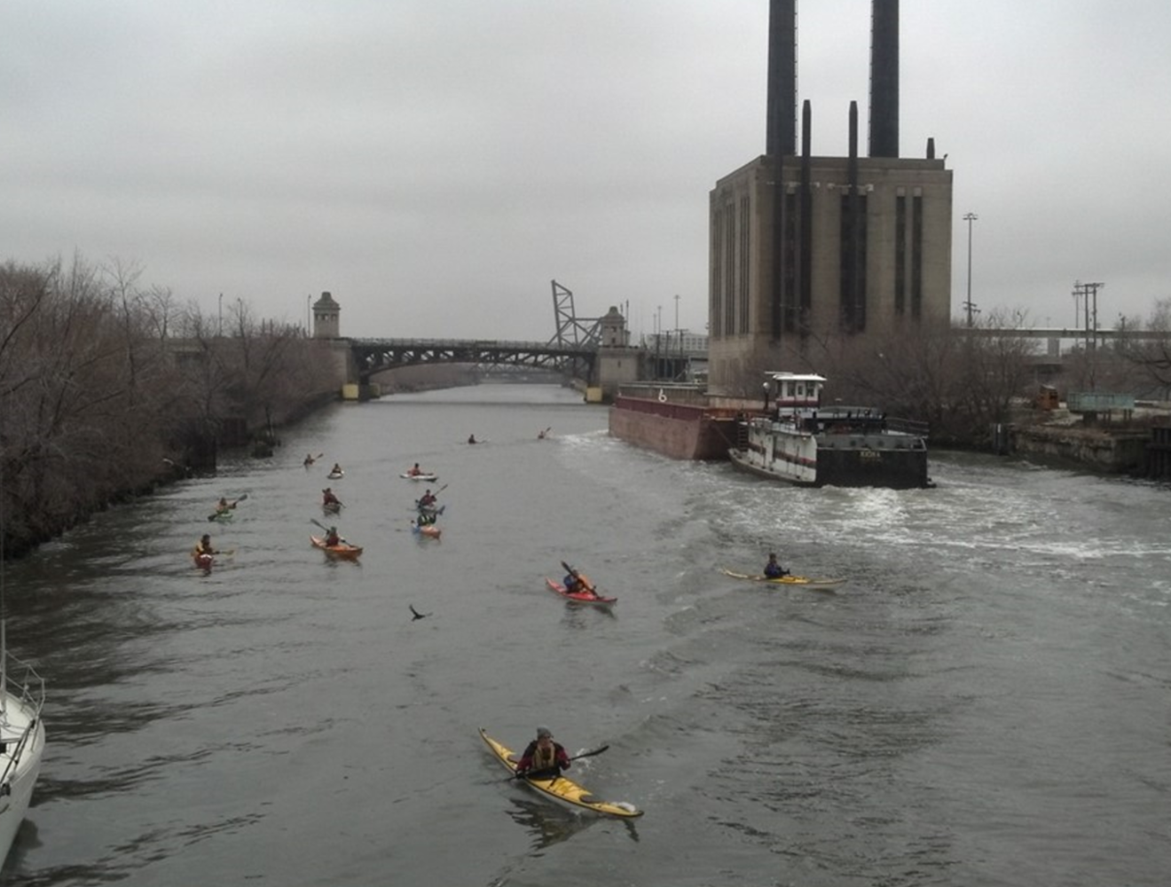In this photo, kayakers are operating in close proximity to a barge and towing vessel in the Chicago River.