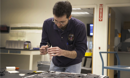 NTSB Materials Engineer Matt Fox examines the casing from the battery involved in the JAL Boeing 787 fire incident in Boston.