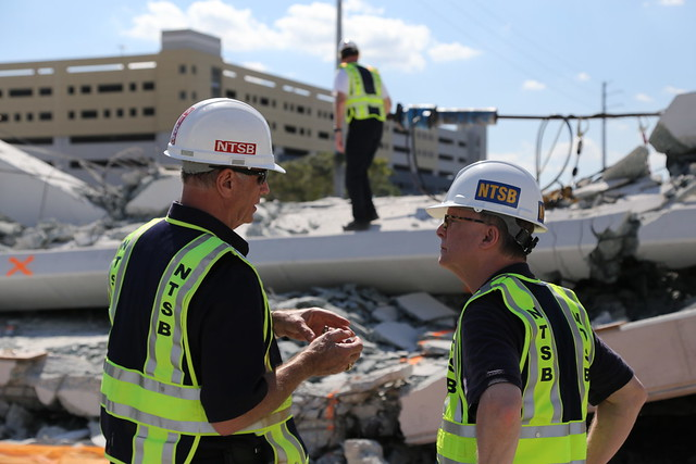 Photo of Investigator-in-Charge Robert Accetta (left) briefs NTSB Chairman Robert Sumwalt on the status of the investigation.
