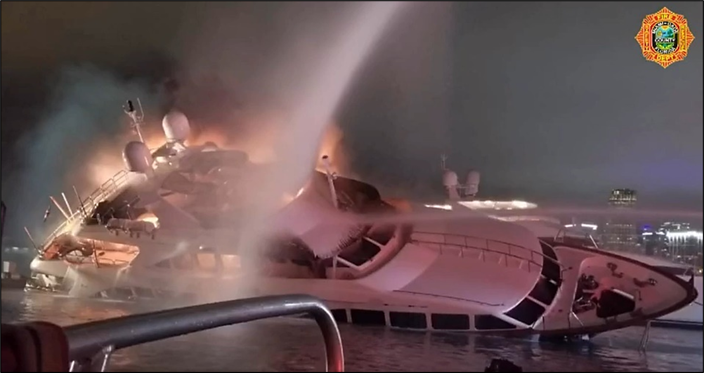 Photo of the yacht Andiamo is seen ablaze and listing to starboard as fireboats attempt to extinguish the fire.